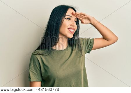 Young hispanic girl wearing casual t shirt very happy and smiling looking far away with hand over head. searching concept.