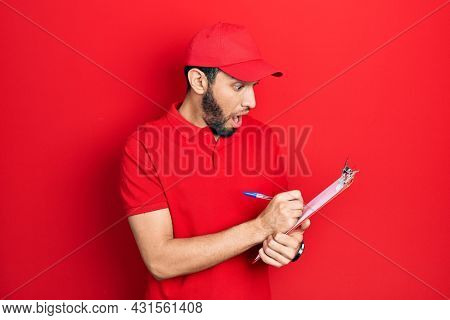 Hispanic man with beard wearing courier uniform holding clipboard afraid and shocked with surprise and amazed expression, fear and excited face.