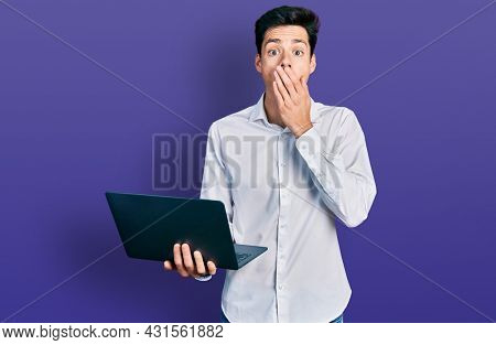 Young hispanic business man working using computer laptop covering mouth with hand, shocked and afraid for mistake. surprised expression