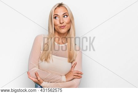 Young blonde woman wearing casual clothes smiling looking to the side and staring away thinking.