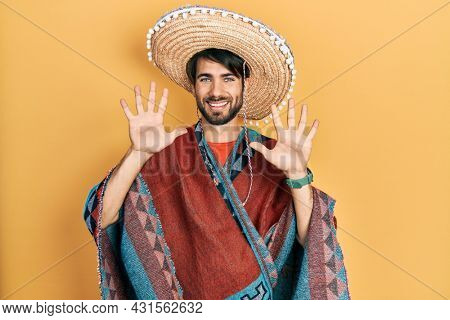 Young hispanic man holding mexican hat showing and pointing up with fingers number ten while smiling confident and happy.