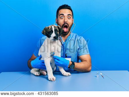 Handsome hispanic veterinary man with beard checking dog health using stethoscope afraid and shocked with surprise and amazed expression, fear and excited face.