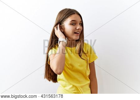 Young brunette teenager standing together over isolated background smiling with hand over ear listening an hearing to rumor or gossip. deafness concept.