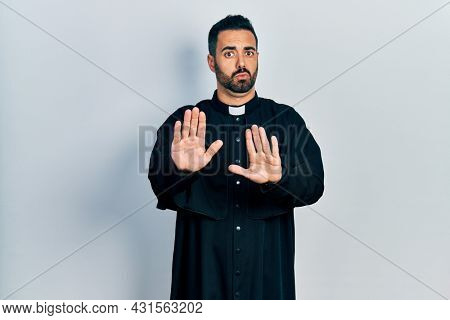 Handsome hispanic man with beard wearing catholic priest robe moving away hands palms showing refusal and denial with afraid and disgusting expression. stop and forbidden.