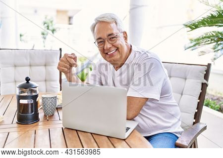 Handsome middle age hispanic man with grey hair and glasses working using computer laptop at home. Smiling happy and confident, relaxed at house terrace.