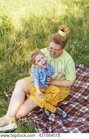 A Mother With A Young Disabled Son Is Resting In A City Park On A Sunny Day. Infantile Cerebral Pals