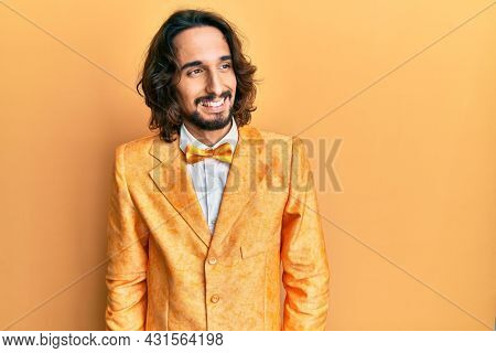 Young hispanic man wearing hipster elegant look looking away to side with smile on face, natural expression. laughing confident.