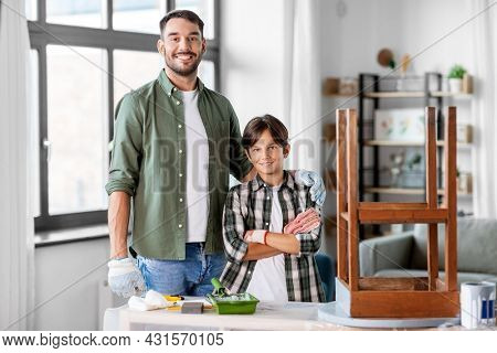family, diy and home improvement concept - happy smiling father and son with ruler restoring old table