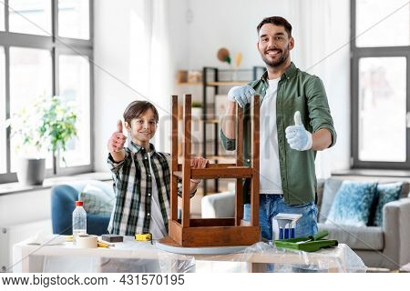 furniture renovation, diy and home improvement concept - happy smiling father showing thumbs up to his son sanding old round wooden table with sponge