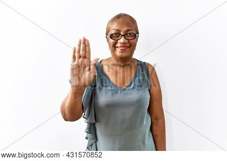 Mature hispanic woman wearing glasses standing over isolated background waiving saying hello happy and smiling, friendly welcome gesture