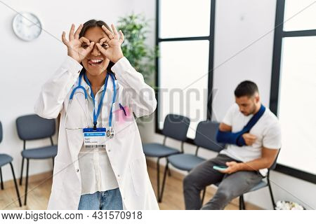 Young asian doctor woman at waiting room with a man with a broken arm doing ok gesture like binoculars sticking tongue out, eyes looking through fingers. crazy expression.