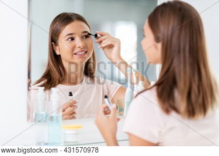 beauty, make up and cosmetics concept - teenage girl applying eye makeup with mascara and looking to mirror at home bathroom