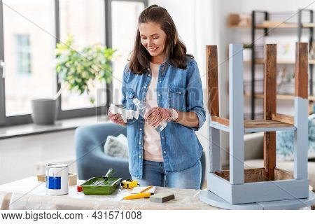 furniture restoration, diy and home improvement concept - happy smiling woman applying solvent to rag for cleaning old wooden table for renovation