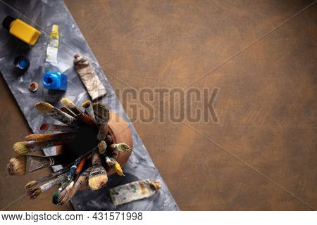 Paint brush in clay jug and art painter tool on abstract background texture. Paintbrush for painting as artistic paint still life. Abstract art concept