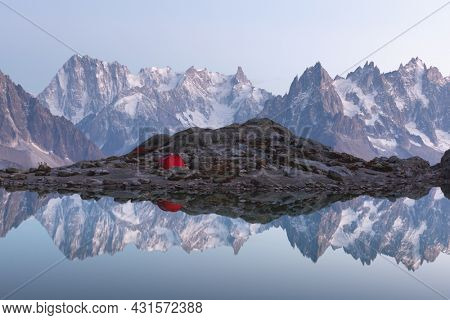 Red tent on Lac Blanc lake coast in France Alps. Monte Bianco mountains range on background. Landscape photography, Chamonix.