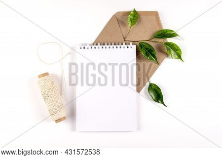 Notebook, Recycled Paper Envelope And Spool Of Plain Coarse Thread Lie On White Surface With Sprig O