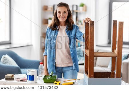 furniture restoration, diy and home improvement concept - happy smiling woman renovating old table
