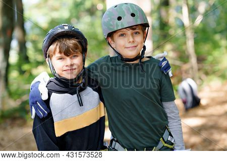 Two Children In Forest Adventure Park. Kids Boys In Helmet Climbs On High Rope Trail. Agility Skills