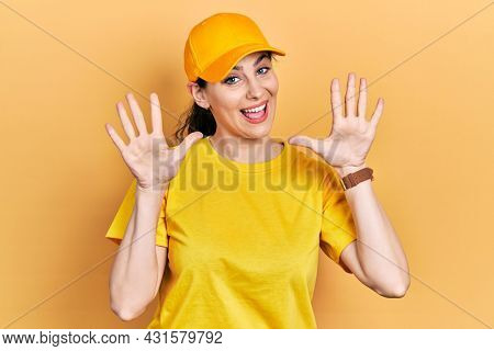 Young hispanic woman wearing delivery uniform and cap showing and pointing up with fingers number ten while smiling confident and happy.
