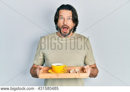 Middle age caucasian man holding breakfast tray with cookies and coffee afraid and shocked with surprise and amazed expression, fear and excited face.