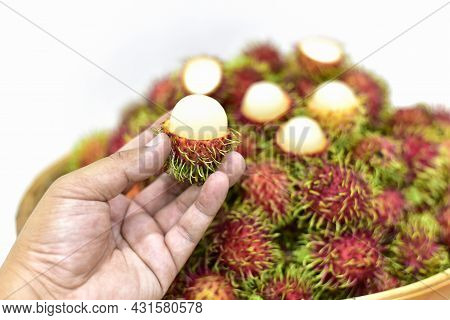 Rambutan Fruit On Hand Harvest From The Garden, Thai Fruits In A Bamboo Basket Placed On White Backg