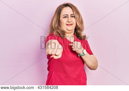 Middle age caucasian woman wearing casual clothes punching fist to fight, aggressive and angry attack, threat and violence
