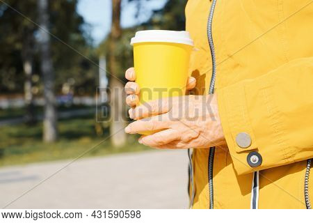 Side View Of Senior Woman In Yellow Jacket Holding Yellow Disposable Cup Of Coffee Or Tea While Walk
