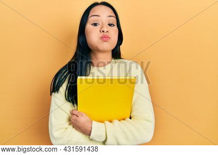 Beautiful hispanic woman with nose piercing holding book puffing cheeks with funny face. mouth inflated with air, catching air.