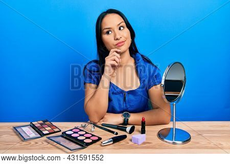 Beautiful hispanic woman with nose piercing getting ready using make up thinking concentrated about doubt with finger on chin and looking up wondering