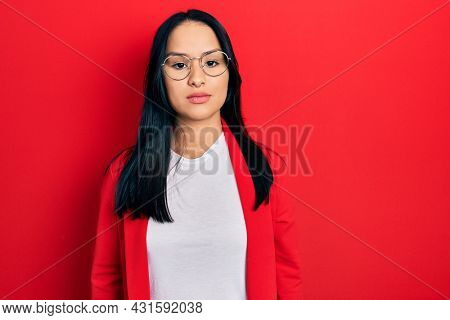 Beautiful hispanic woman with nose piercing wearing casual look and glasses relaxed with serious expression on face. simple and natural looking at the camera.