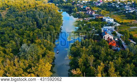 Photo from a drone of a beautiful summer landscape over the river. Beautiful summer landscape with a wide river and green coastline. Aerial photography of the suburban landscape.