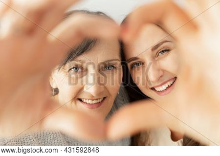 Close-up Portrait Of Lovely Senior Mother And Grown Daughter Look At The Camera Through Heart From P