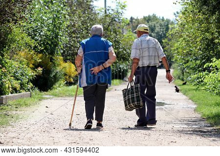 Elderly Couple Walking O A Rural Street. Old Man And Woman With Cane Together, Life In Retirement