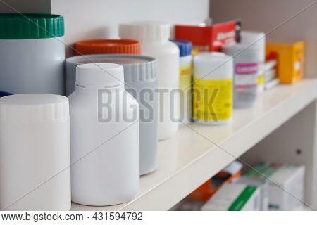 Bottles Of Medicine Pills Arranged On Shelf At Drugstore