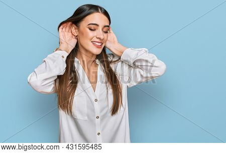 Young beautiful woman wearing casual white shirt trying to hear both hands on ear gesture, curious for gossip. hearing problem, deaf