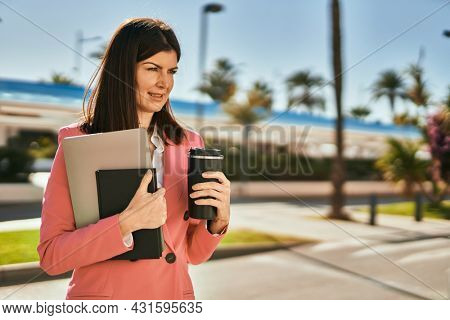 Middle age business woman smilling happy outdoors. Executive holding laptop drinking a take away cup of coffee