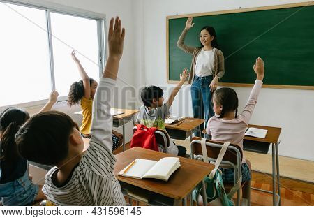 Group Of Diversity Of Elementary School Kids Raise Arm Up To Answer Teacher Question In Classroom. E