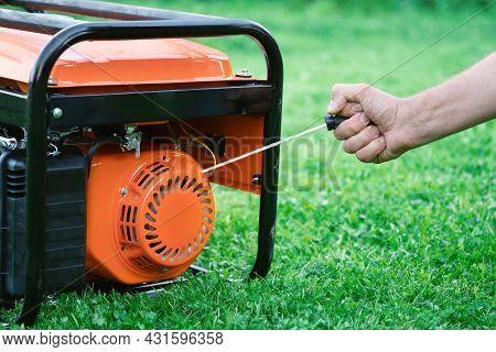 Hand Starts A Portable Gasoline Electric Generator Standing On The Green Grass