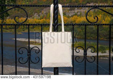 Canvas Tote Bag Hanging On The Park Fence Mockup. Rustic Linen Shopper Bag Mock Up For Branding Pres