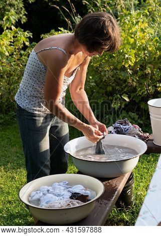 Woman Washes Clothes With Her Hands In Old Basin Outdoors At Countryside In Summer Evening.