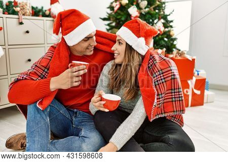 Young couple wearing christmas hat covering with blanket. Sitting on the floor drinking coffee at home.