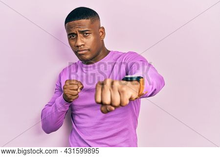 Young black man wearing casual pink sweater punching fist to fight, aggressive and angry attack, threat and violence