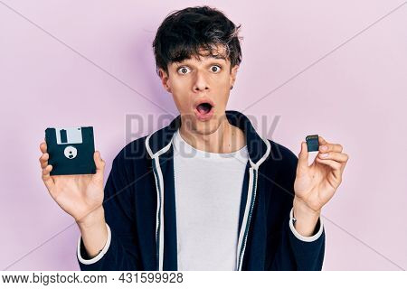 Handsome hipster young man holding floppy disk and sdxc card afraid and shocked with surprise and amazed expression, fear and excited face.