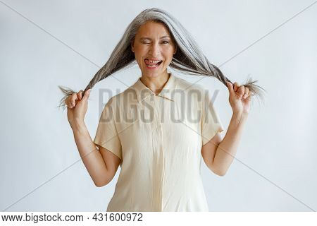 Middle Aged Asian Lady Grimaces And Holds Long Silver Hair On Light Grey Background
