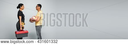 Side View Of African American Father Holding Baby Covered In Blanket Near Repairwoman With Toolbox O