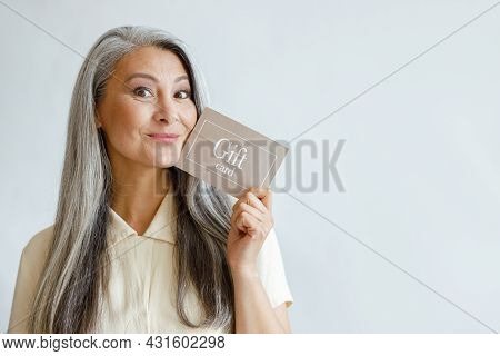 Joyful Grey Haired Asian Woman Holds Gift Card Posing On Light Grey Background