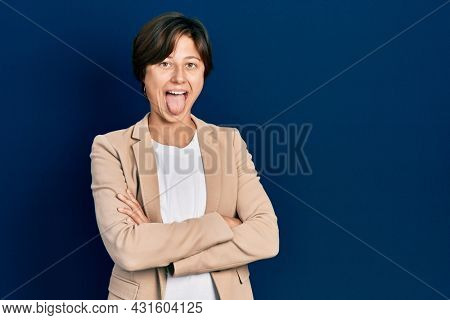 Young caucasian woman with arms crossed gesture sticking tongue out happy with funny expression.
