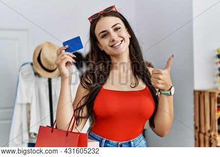 Young brunette woman holding shopping bags and credit card smiling happy and positive, thumb up doing excellent and approval sign