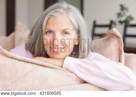 Happy woman relaxing on couch at home in living room. Portrait of beautiful mature female smiling while sitting at sofa at home. Beautiful middle age lady smiling and looking at camera at home
