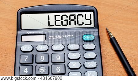 On A Wooden Table There Is A Black Pen And A Calculator With The Text Legacy. Business Concept